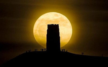 Revellers stand beside St. Michael's Tower on Glastonbury Tor watching the moon as it is at its closest point to the Earth for almost two decades.Photo Credit: The Telegraph