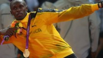 Usain Bolt celebrates winning his third gold