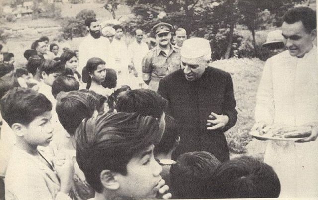 Nehru distributing sweets to children