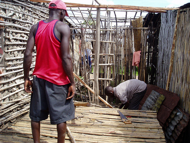 People constructing a bamboo house