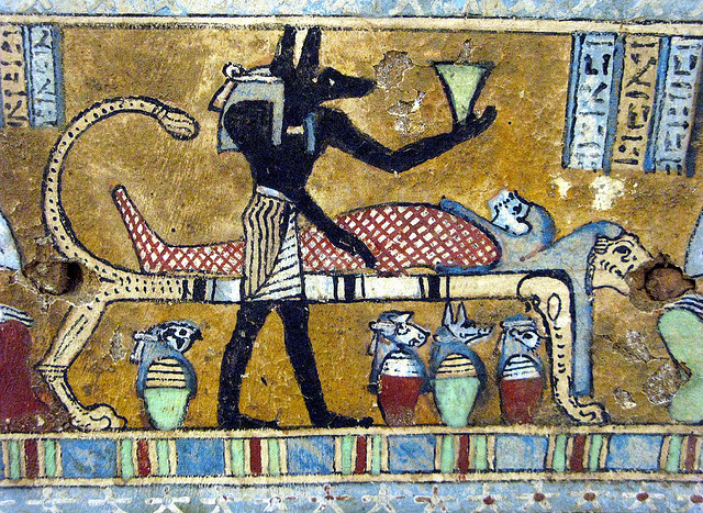 Priest with a jackal mask doing mummification in ancient Egypt